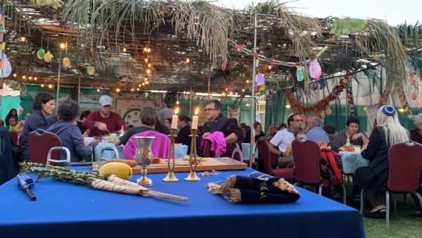 Community celebrating in the sukkah