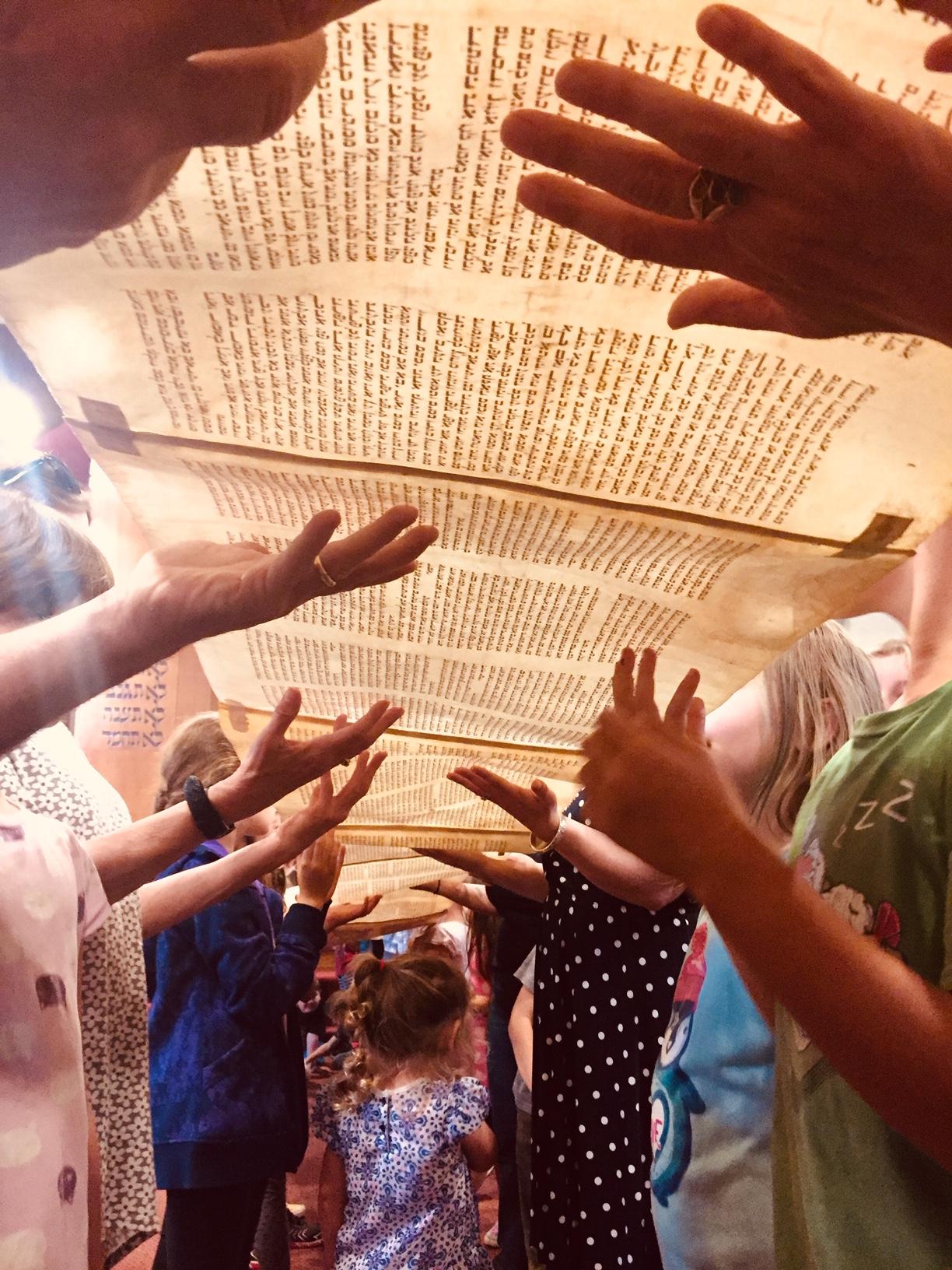 Torah unrolled hands lifting